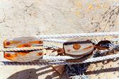 Envelhecido oxidada roldana de madeira no porto de mediterrantan — Foto Stock