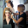 Backstage hairdressing fashion with make-up artist - Stockfoto