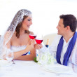 Couple in wedding day cheering with red wine — Stock Photo