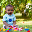 Little african american baby boy playing in the grass — Stock Photo #10967975