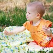 Beautiful little girl in orange dress sitting on a meadow — Stock Photo