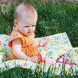 Cute little blonde girl in orange dress playing on a meadow — Stock Photo