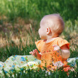 Cute little girl in orange dress sitting on meadow — Stock Photo #11246223