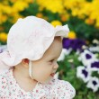 Portrait of a beautiful little girl in panama in the flower background — Stock Photo