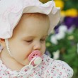 Portrait of a cute little girl with a pacifier in panama in the flower background — Stock Photo