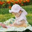 Beautiful little girl in a hat sitting on a flowers meadow — Stock Photo