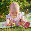 Beautiful little blond girl sitting on meadow — Stock Photo #11246848