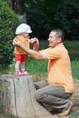 Папа держит маленькую дочь за руку, стоя на пень в парке — Стоковое фото