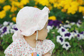 Portrait of a cute little girl in panama in the flower background — Stock Photo