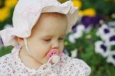 Panama çiçek arka planda bir emzik ile sevimli küçük bir kız portresi — Stok fotoğraf