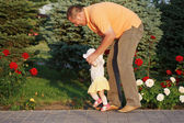 Daddy teaches her beautiful daughter to walk on the background of rose bushes — Stock Photo
