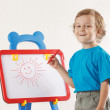 Little cute smiling boy drew a sun on the whiteboard — Stock Photo #11415239