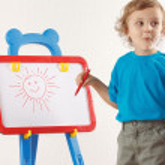 Little cute blond boy drew a sun on the whiteboard — Stock Photo #11415252