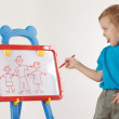 Little smiling cute boy drew a family on a whiteboard — Stock Photo #11415267