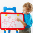 Little cute blond boy shows his family painted on whiteboard — Stock Photo