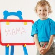 Stock Photo: Little cute smiling boy wrote word mamon whiteboard