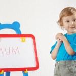 petit garçon mignon a écrit la mot maman sur un tableau blanc — Photo #11415468