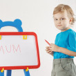 Little cute smiling boy wrote the word mum on a whiteboard — Stock Photo
