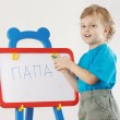 Little cute smiling boy wrote the word papa on a whiteboard — Foto de Stock   #11415570