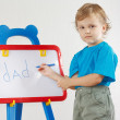 Little cute boy wrote the word dad on whiteboard — Stock Photo #11415597