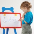 Little cute blond boy wrote the word daddy on a whiteboard — Stock Photo
