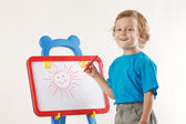 Little cute smiling boy drew a sun on the whiteboard — Foto Stock