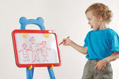 Little smiling cute boy drew a family on a whiteboard — Stock Photo