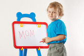 Little cute smiling boy wrote the word mom on a whiteboard — Stock Photo