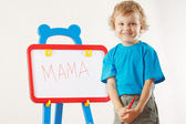 Little cute smiling boy wrote the word mama on a whiteboard — Stock Photo