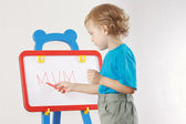 Little cute blond boy wrote the word mum on whiteboard — Stock Photo