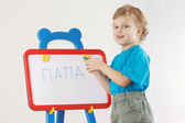 Little cute smiling boy wrote the word papa on a whiteboard — Zdjęcie stockowe