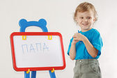 Little smiling boy wrote the word papa on a whiteboard — Zdjęcie stockowe