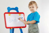 Little cute boy wrote the word dad on whiteboard — Stock Photo