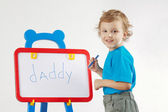 Little smiling boy wrote the word daddy on a whiteboard — Zdjęcie stockowe