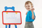 Little cute smiling boy wrote the word daddy on a whiteboard — 图库照片
