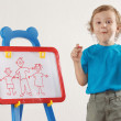Little smiling boy drew a family on a whiteboard — Stock Photo #11426497