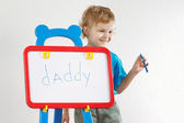Little cute smiling boy wrote the word daddy on a whiteboard — ストック写真