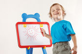 Little smiling boy drew a sun on the whiteboard — Zdjęcie stockowe