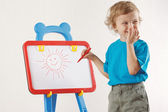 Little smiling blond boy drew a sun on the whiteboard — Zdjęcie stockowe