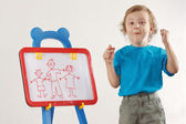Little smiling boy drew a family on a whiteboard — Stock Photo