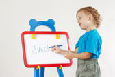 Little cute smiling boy wrote the word dad on a whiteboard — Foto de Stock