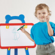 Foto Stock: Little cute smiling boy drew dollar sign on whiteboard