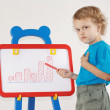 Stock Photo: Little cute serious boy drew diagram of the growth on the whiteboard