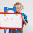Little cute smiling boy shows the word sale on whiteboard — ストック写真