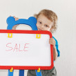 Little cute boy shows the word sale on whiteboard — Stock Photo