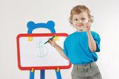 Lilla söta leende pojken drog dollartecken på whiteboard-tavlan — Stockfoto