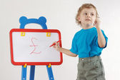 Little cute smiling boy drew pound sign on the whiteboard — Stock Photo