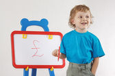 Little smiling blond boy drew pound sign on the whiteboard — Stock Photo