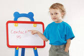 Little cute smiling boy shows the word contact us on whiteboard — Stock Photo