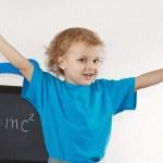 Little boy shows Einstein's formula on blackboard — Stock Photo